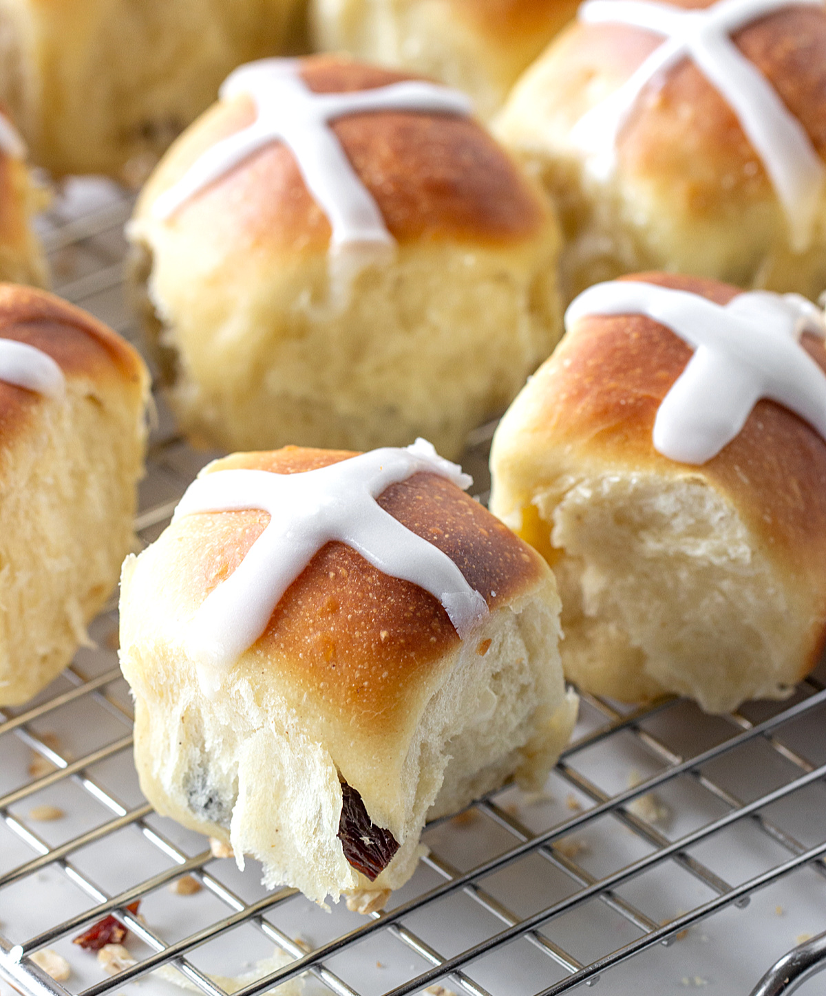 Small buns with white cross on top on wire rack
