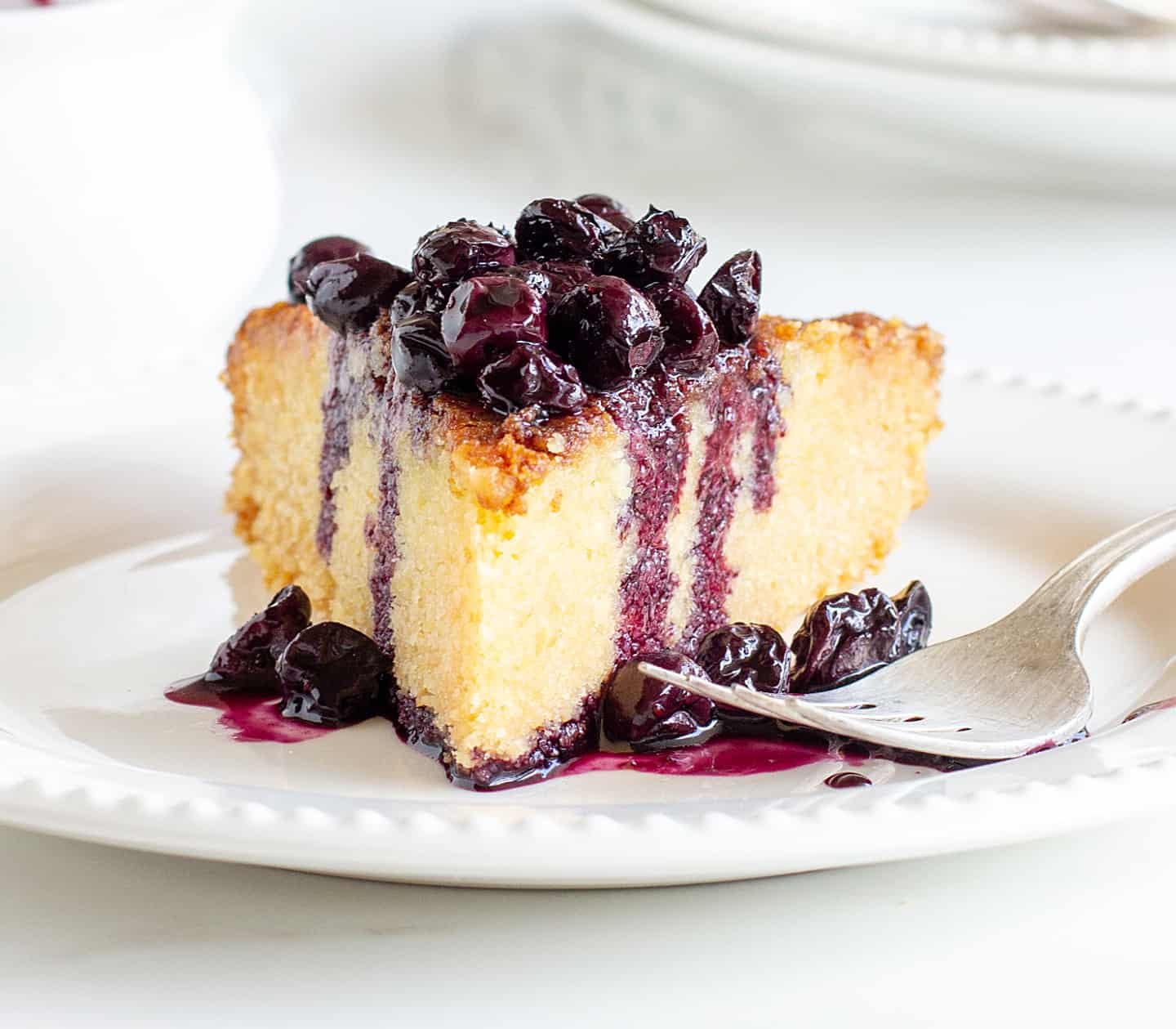 Slice of lemon cake with blueberry sauce on white plate, silver fork, white props on background