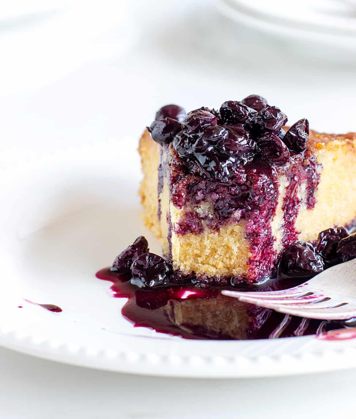 Eaten slice of polenta cake, a pool of blueberry sauce, white plate, silver fork