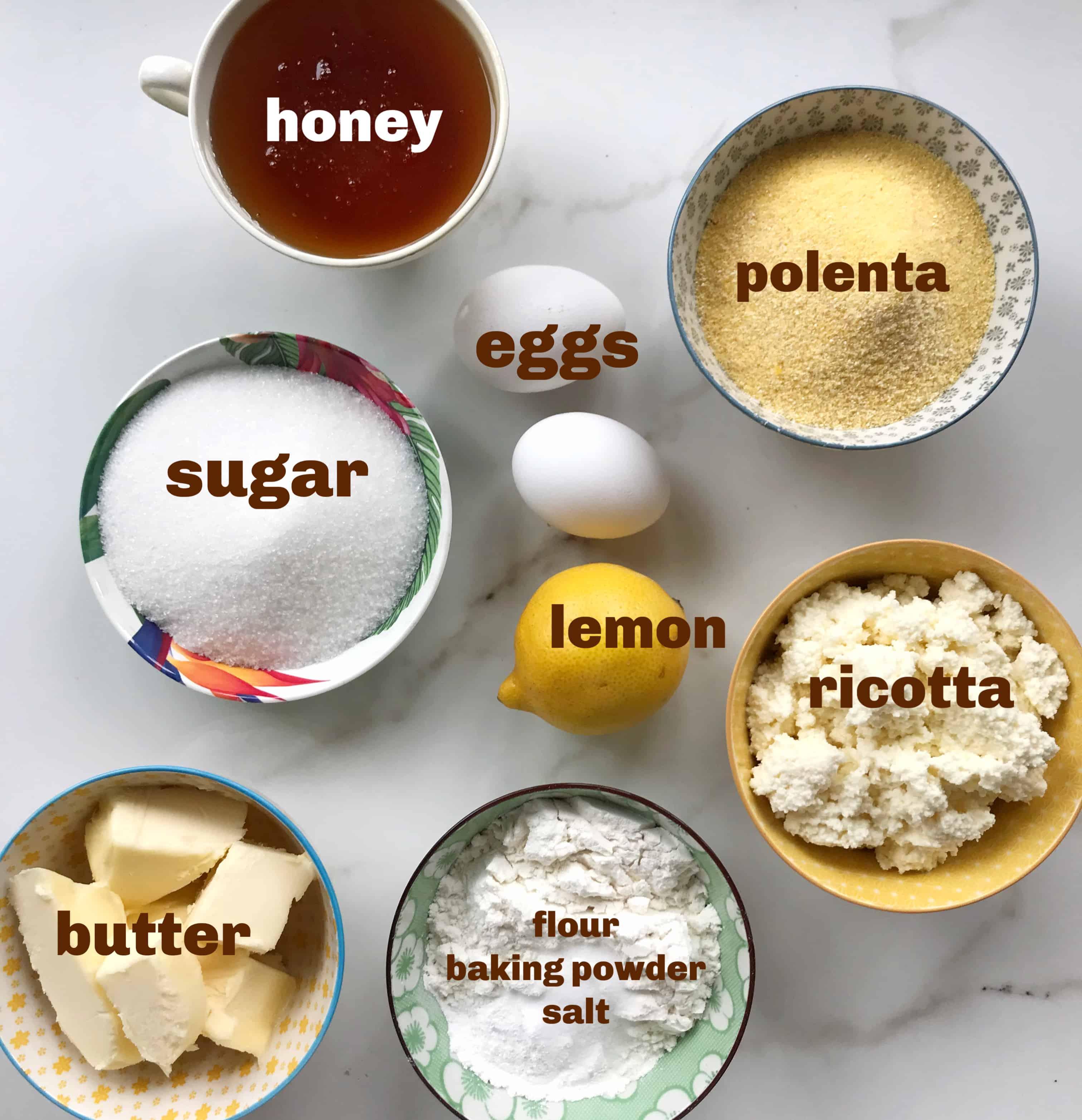 lemon polenta ricotta cake ingredients in bowls on white surface