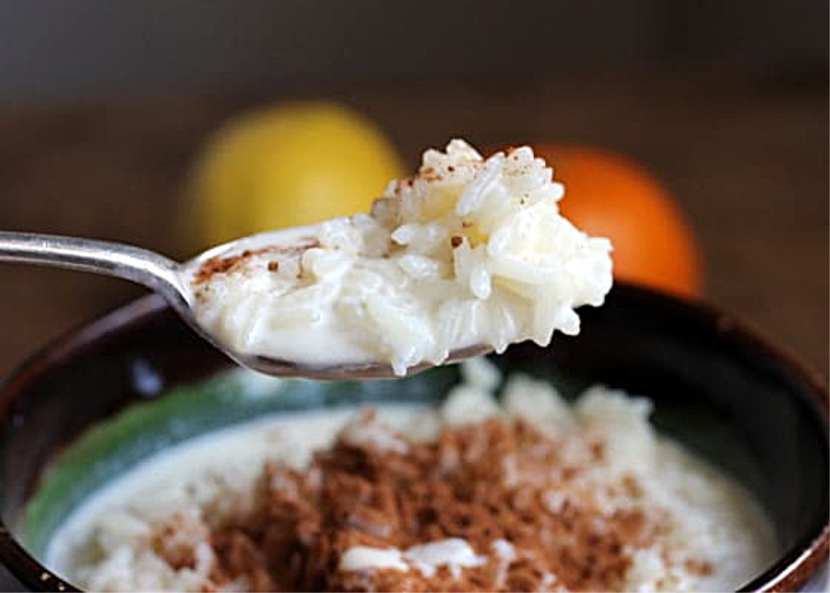 Spoon with rice pudding, bowl and citrus below