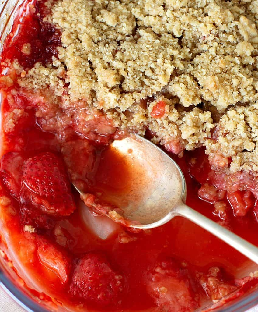 Silver spoon in pool of strawberry crisp on glass dish