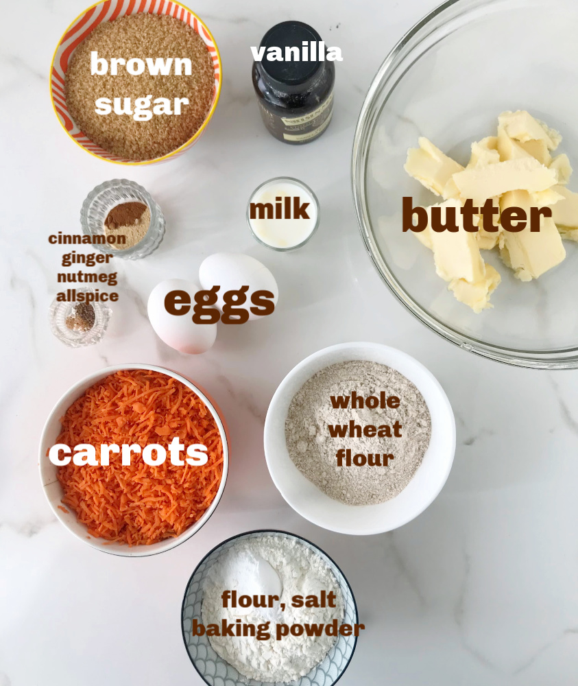 Carrot cake ingredients in small bowls on white surface