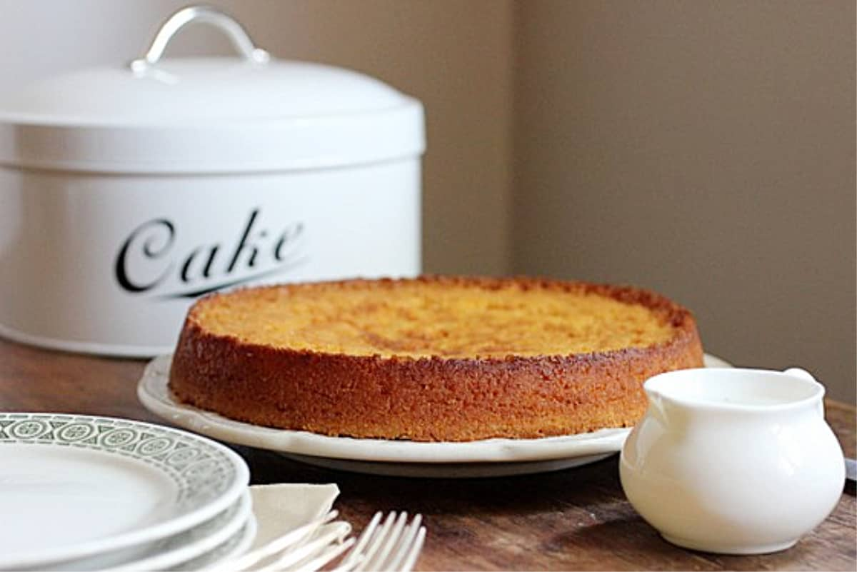 Whole short Lemon Cake on wooden table, stack of plates, saucer, cake tin in background