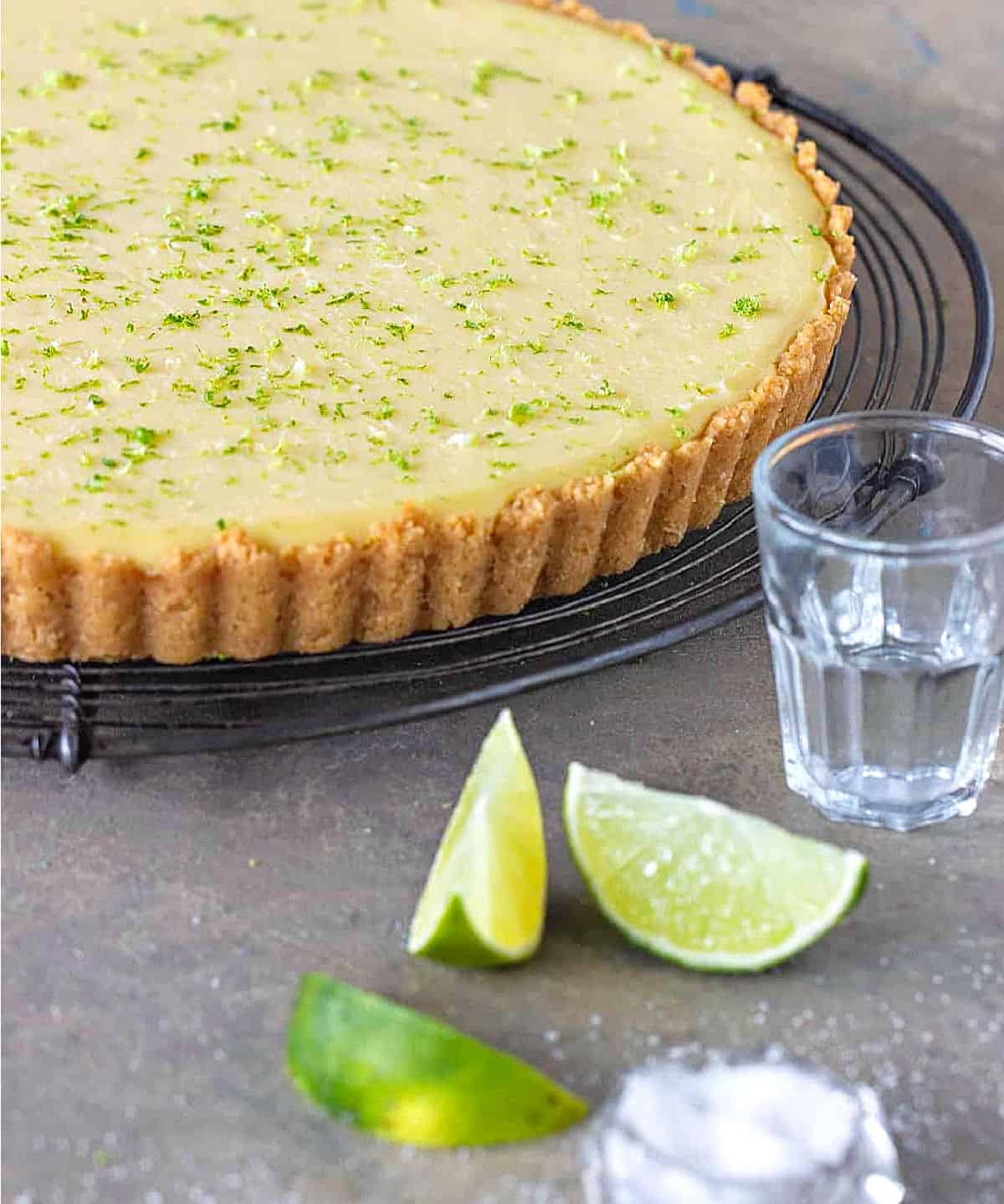 Partial view of lime pie on wire rack, cut limes, salt and glass on grey surface