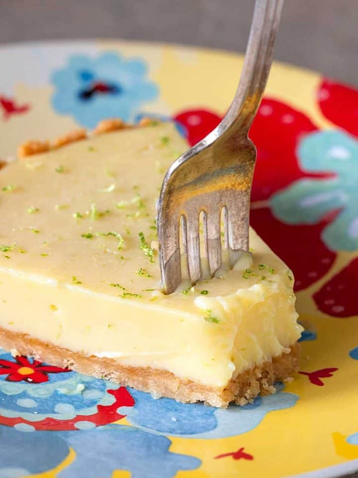 Slice of lime pie and fork on colorful plate