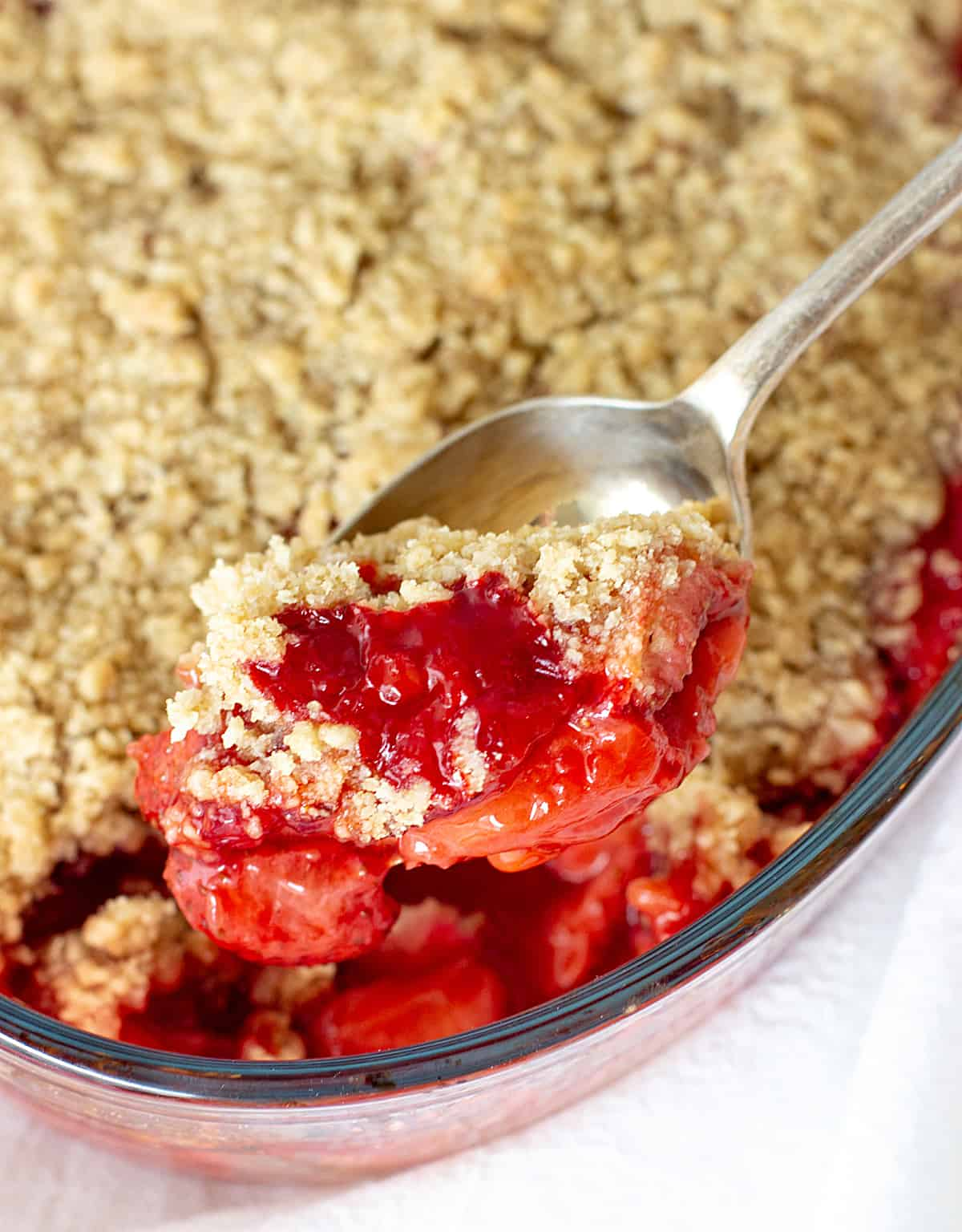 Lifting stawberry crisp portions with a silver spoon from glass dish