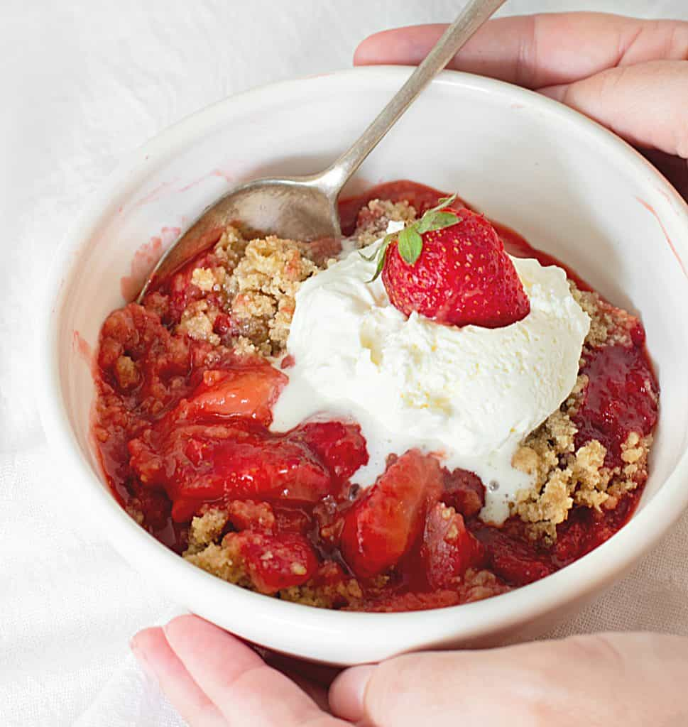 Hands holding a white bowl with strawberry crisp and ice cream, a silver spoon