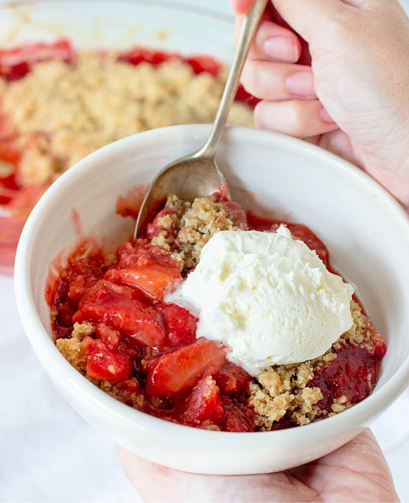 A hand holding a spoon in a white bowl with strawberry crumble dessert and scoop of ice cream