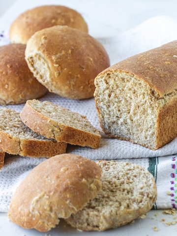 Loaf bread and buns on white kitchen towel, whole and sliced