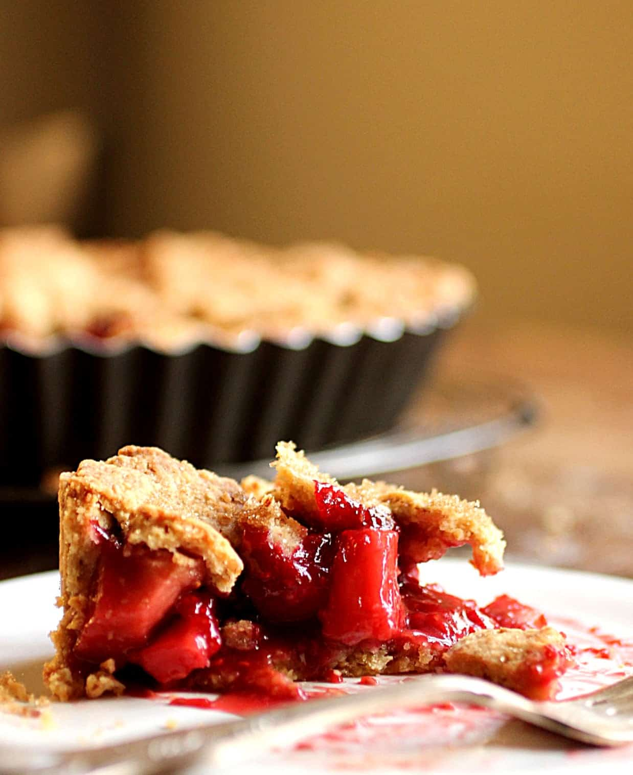 Slice of apple raspberry pie on white plate, pie pan and wooden table on background