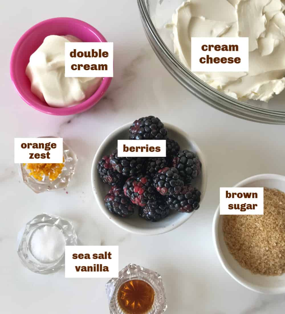 Ingredients for cheesecake berry ice cream in bowls on white surface