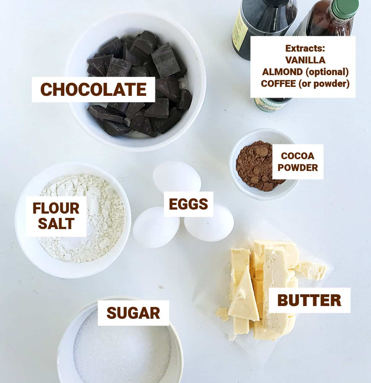 White surface with bowls containing brownie ingredients, like eggs, extract bottles, image with text