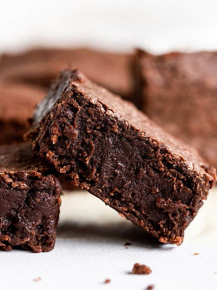 Several plain fudgy Brownie squares on white surface
