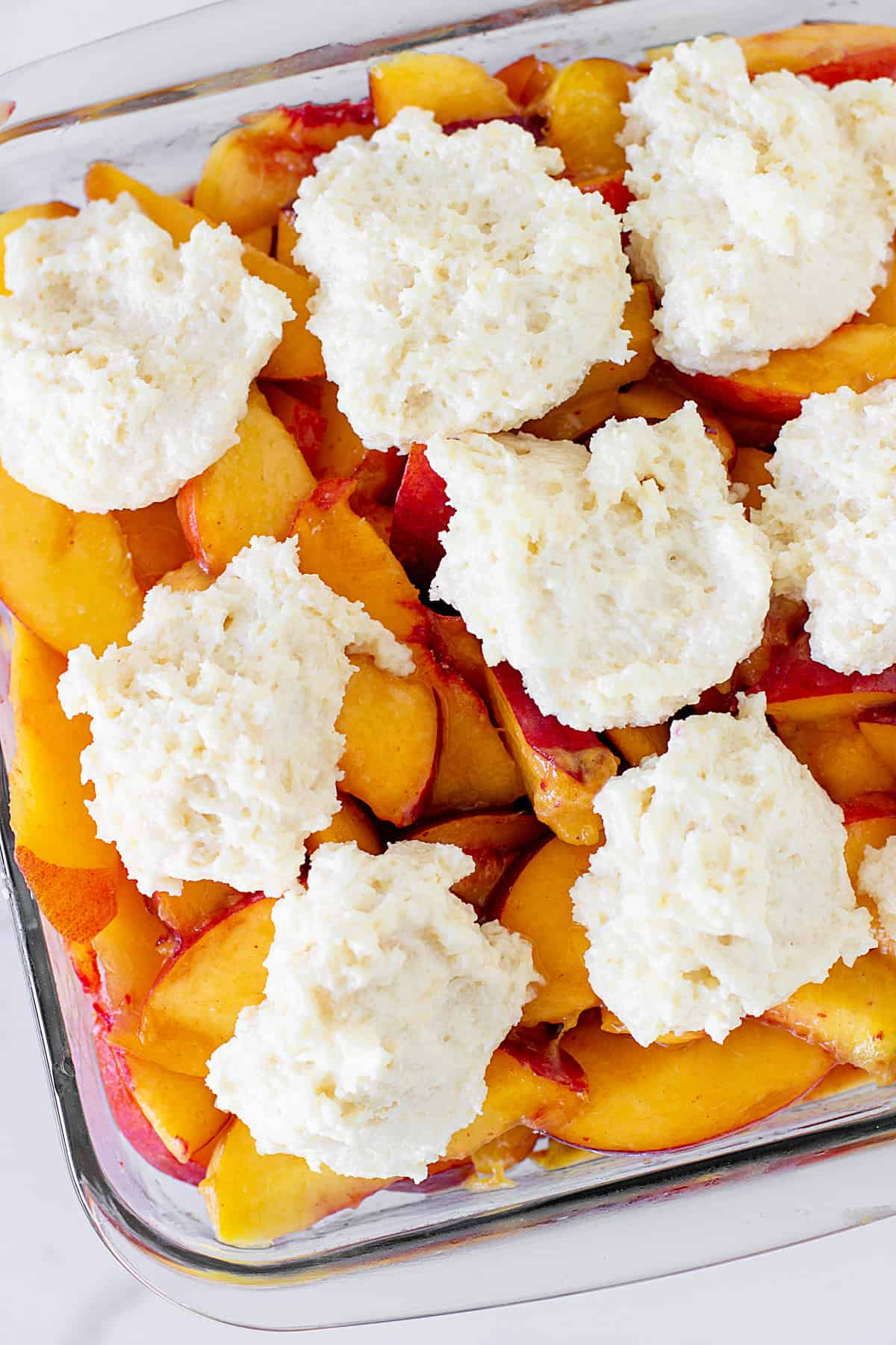 Glass dish with peaches and raw biscuit topping