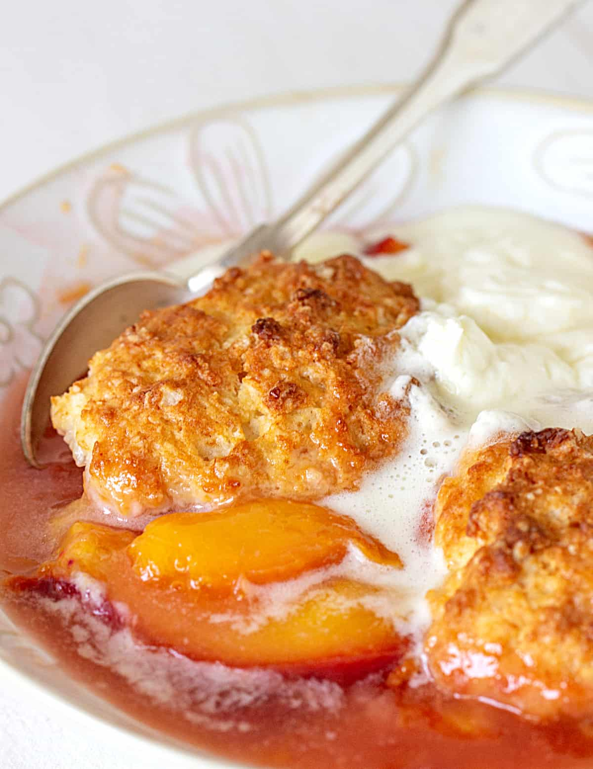 White bowl with juicy peach cobbler, scoop of ice cream, silver spoon
