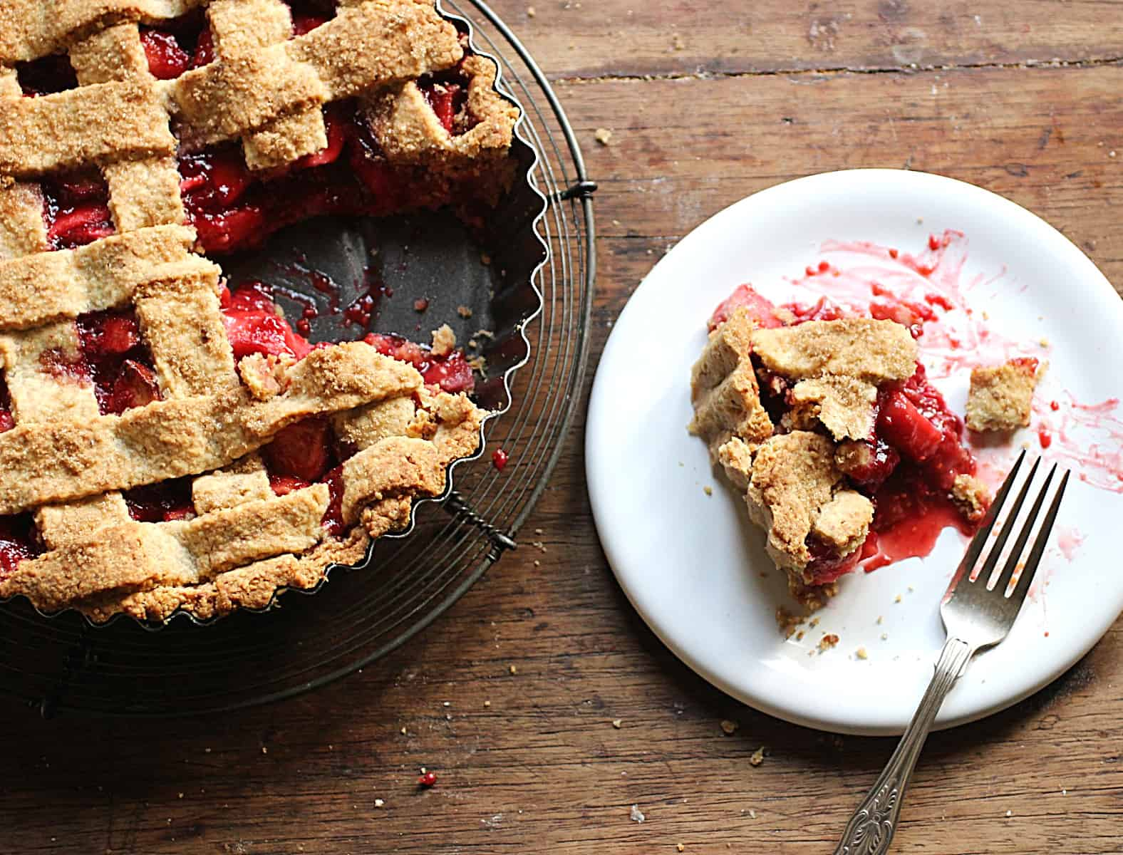 Raspberry Apple Pie in pan, one slice on white plate, wooden table