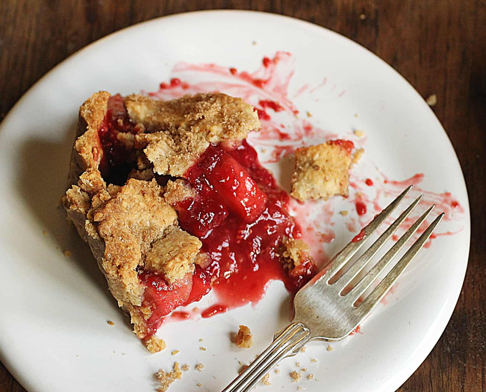Slice of raspberry apple pie on white plate, silver fork, wooden table
