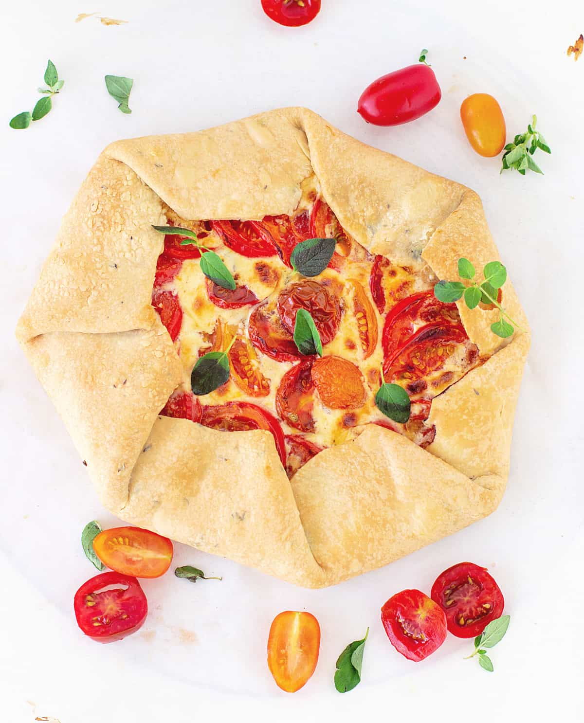 Whole tomato galette on white surface, loose cherry tomatoes and herbs around it