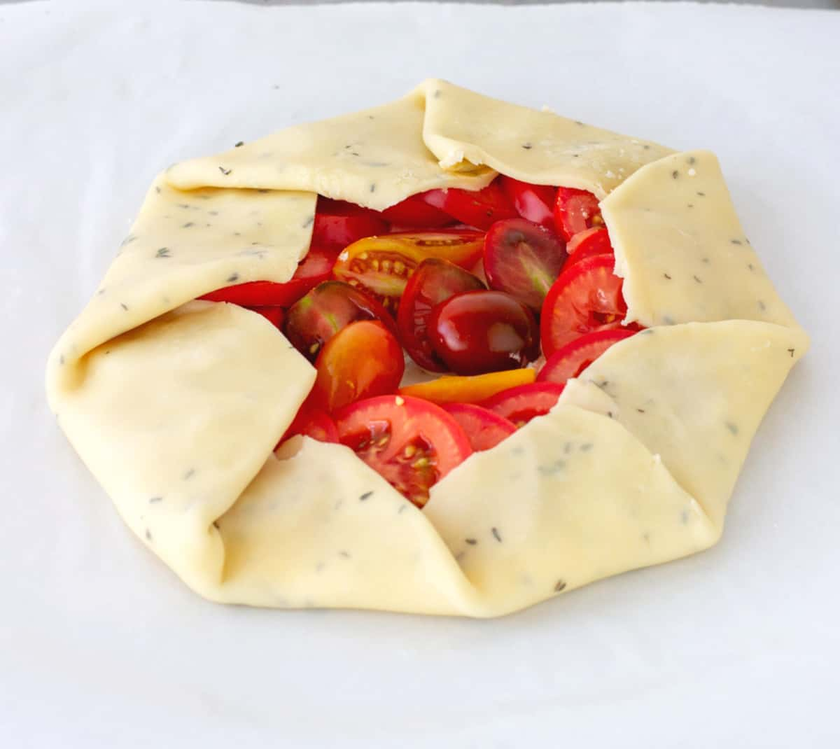 Unbaked tomato galette on white paper