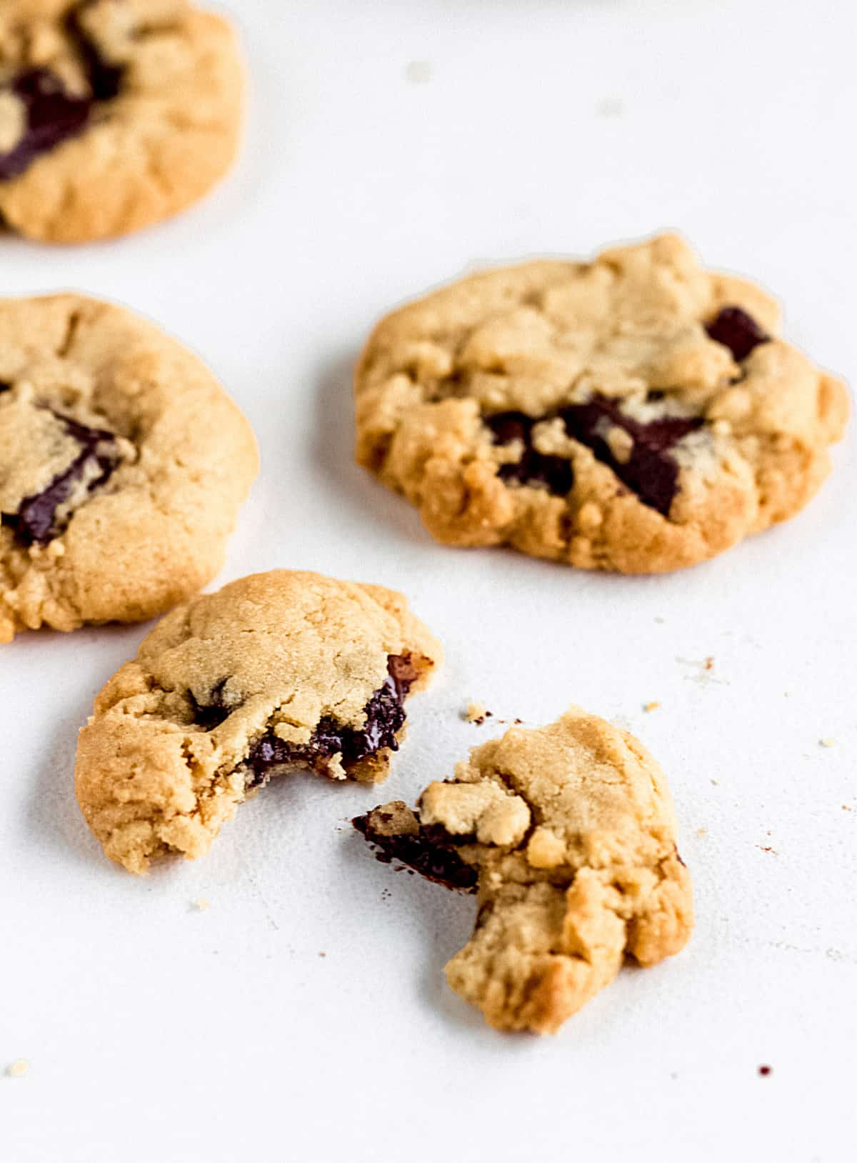 Cookie with chocolate chunks cut in half and whole ones on a white surface