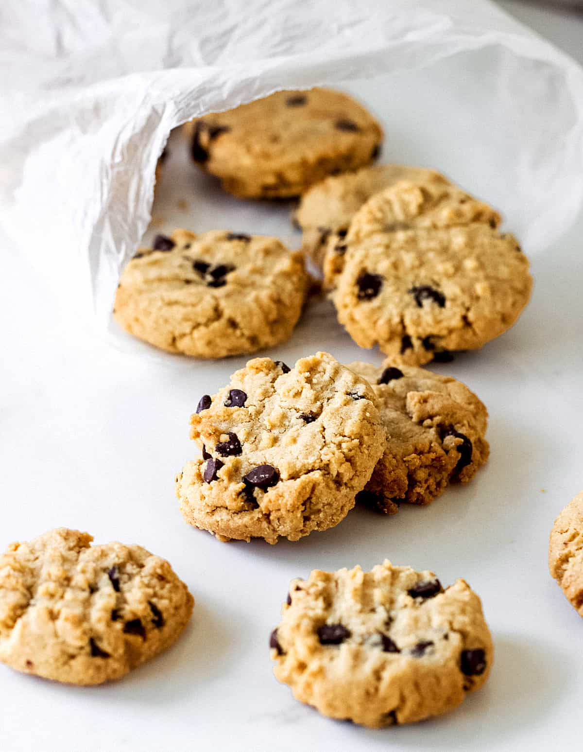 Round cookies with chocolate chips on a white table coming out from a plastic bag