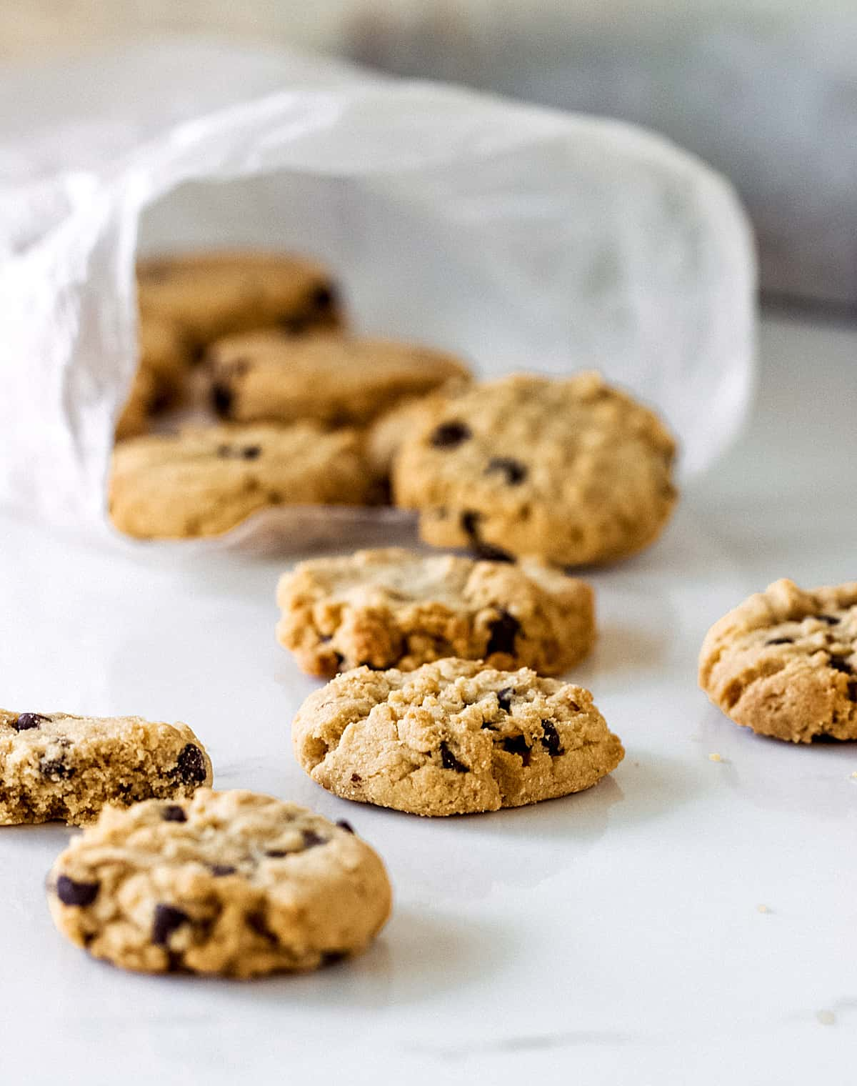 Cookies coming out of a plastic bag on a white surface