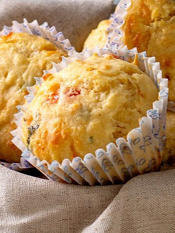 Whole muffins in paper cups on top of a beige piece of linen