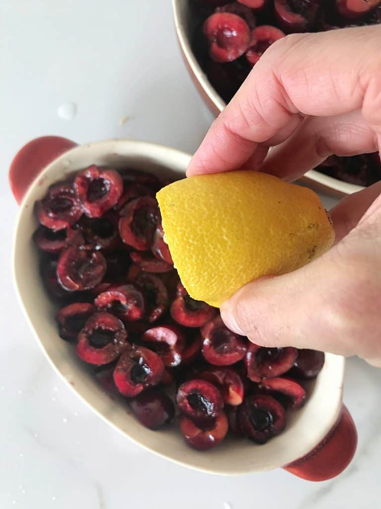 Hand adding lemon juice to cherries in oval dish below