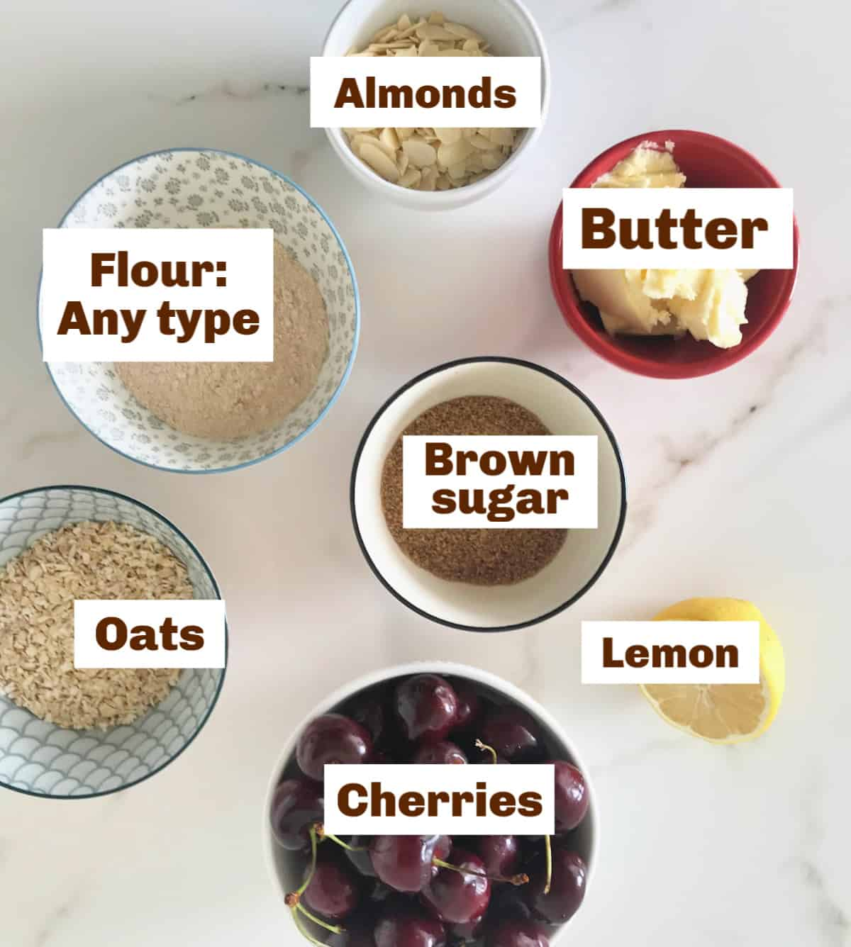 Bowls with ingredients, cherries, a half lemon, white surface