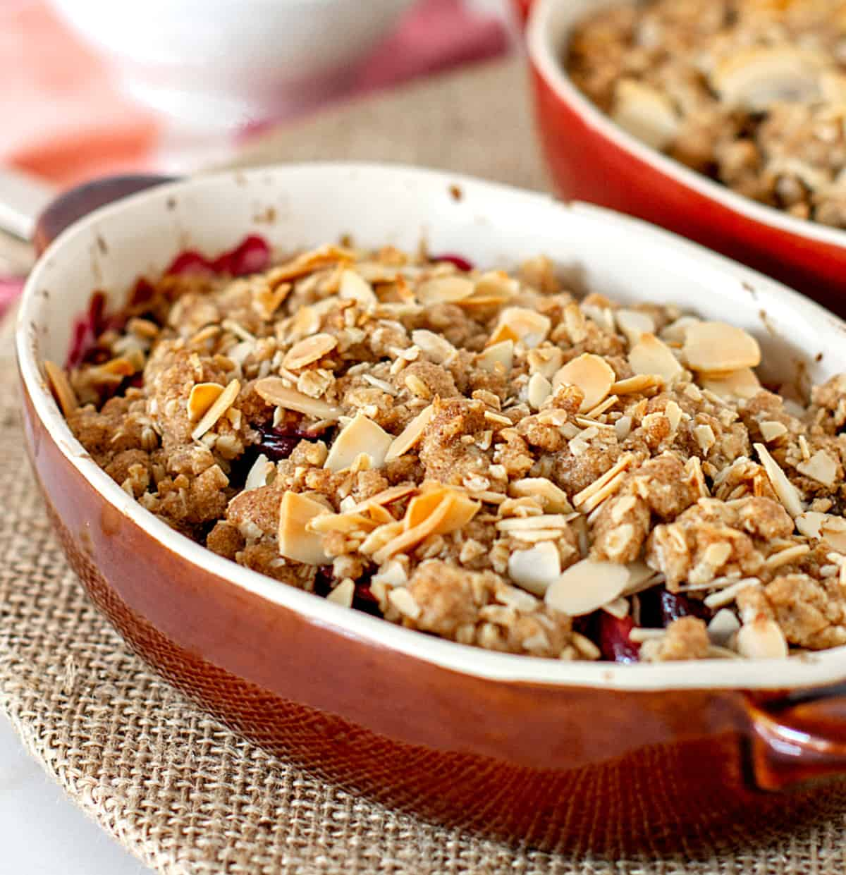 Brown oval dish with baked crumble, burlap surface
