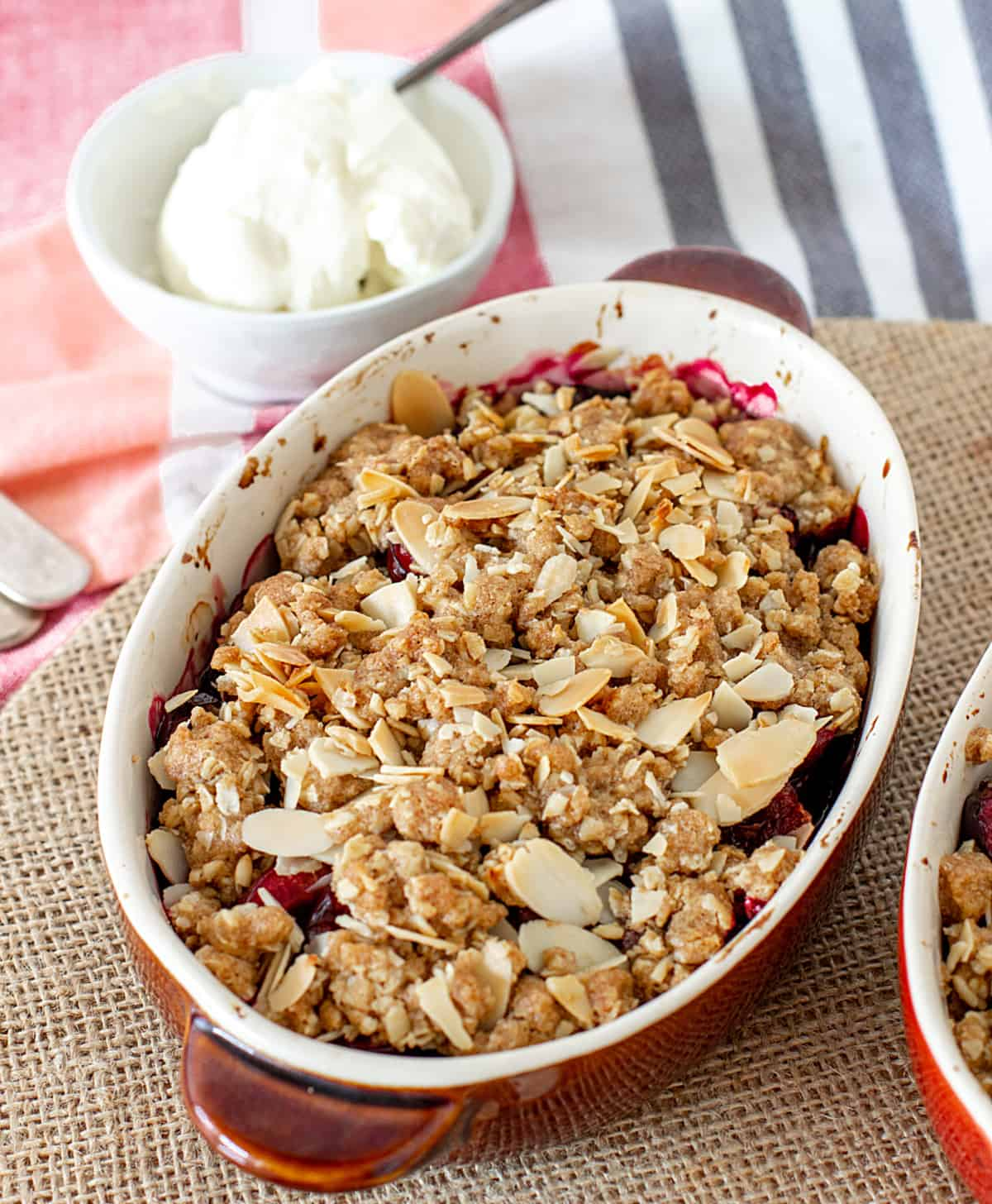 Brownish oval baked crumble on burlap surface, bowl with cream and striped towel in background