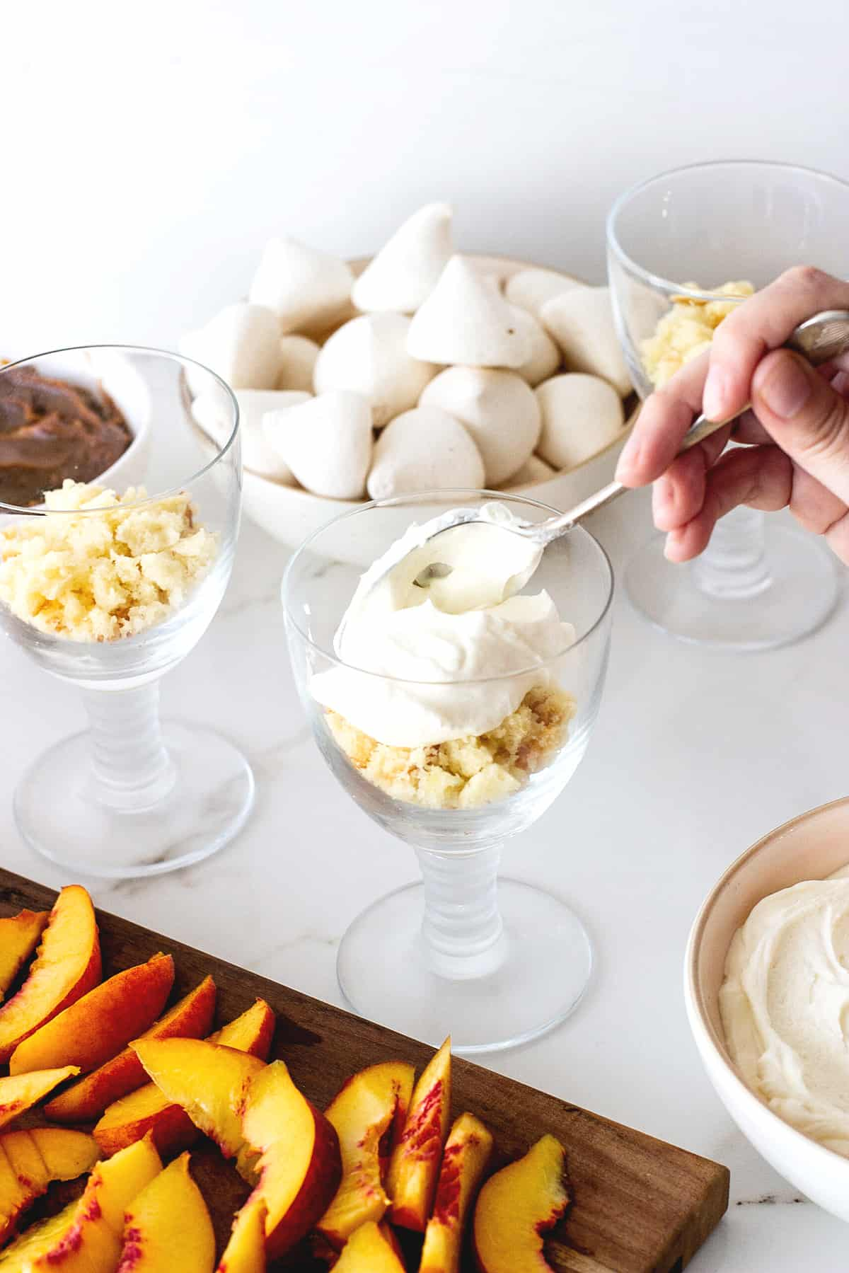Hand adding cream to stem glass pn white surface; peaches, meringues, and rest of dessert around