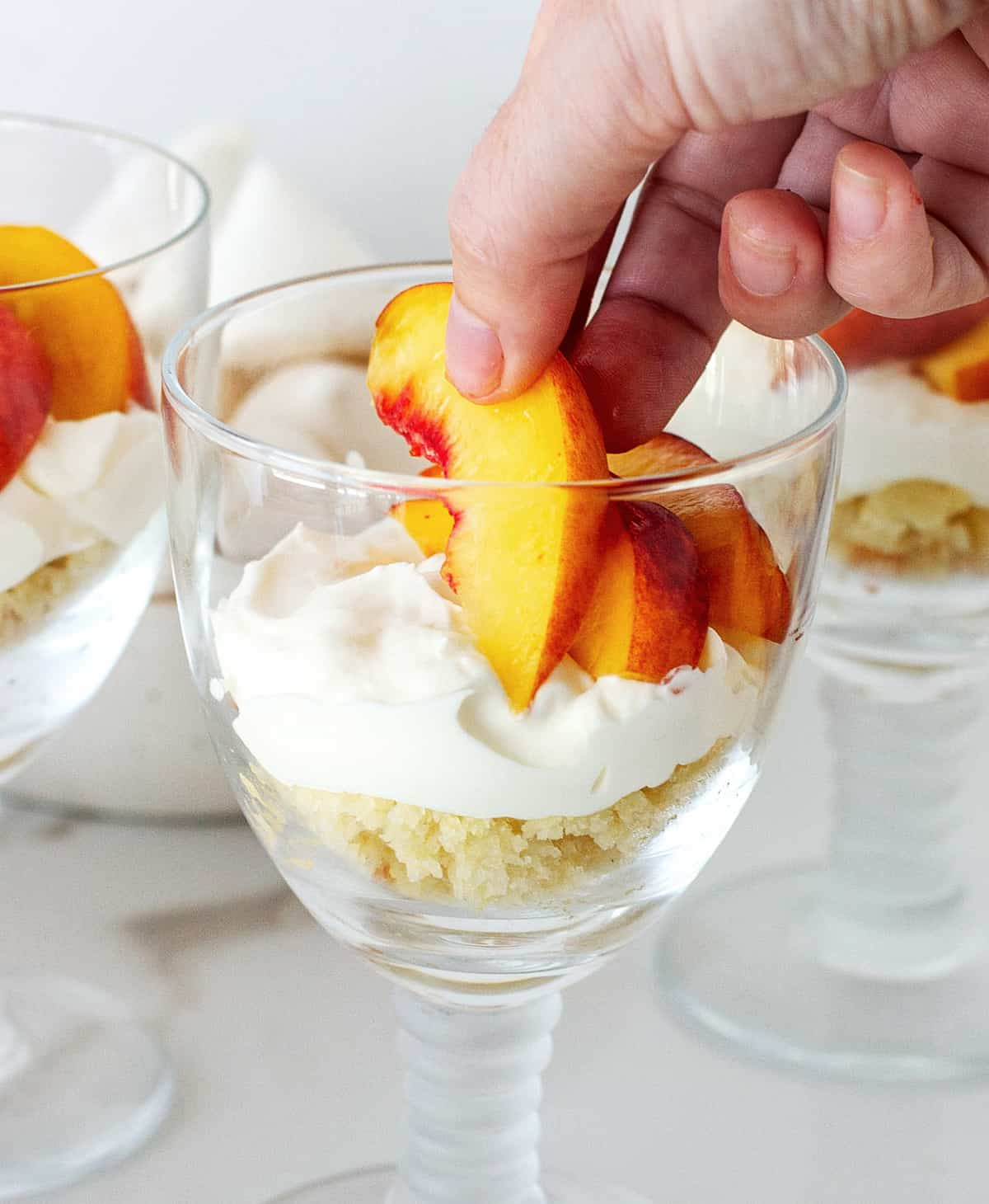 Close up of hand adding slice of yellow peach to stem glass with cream; white background