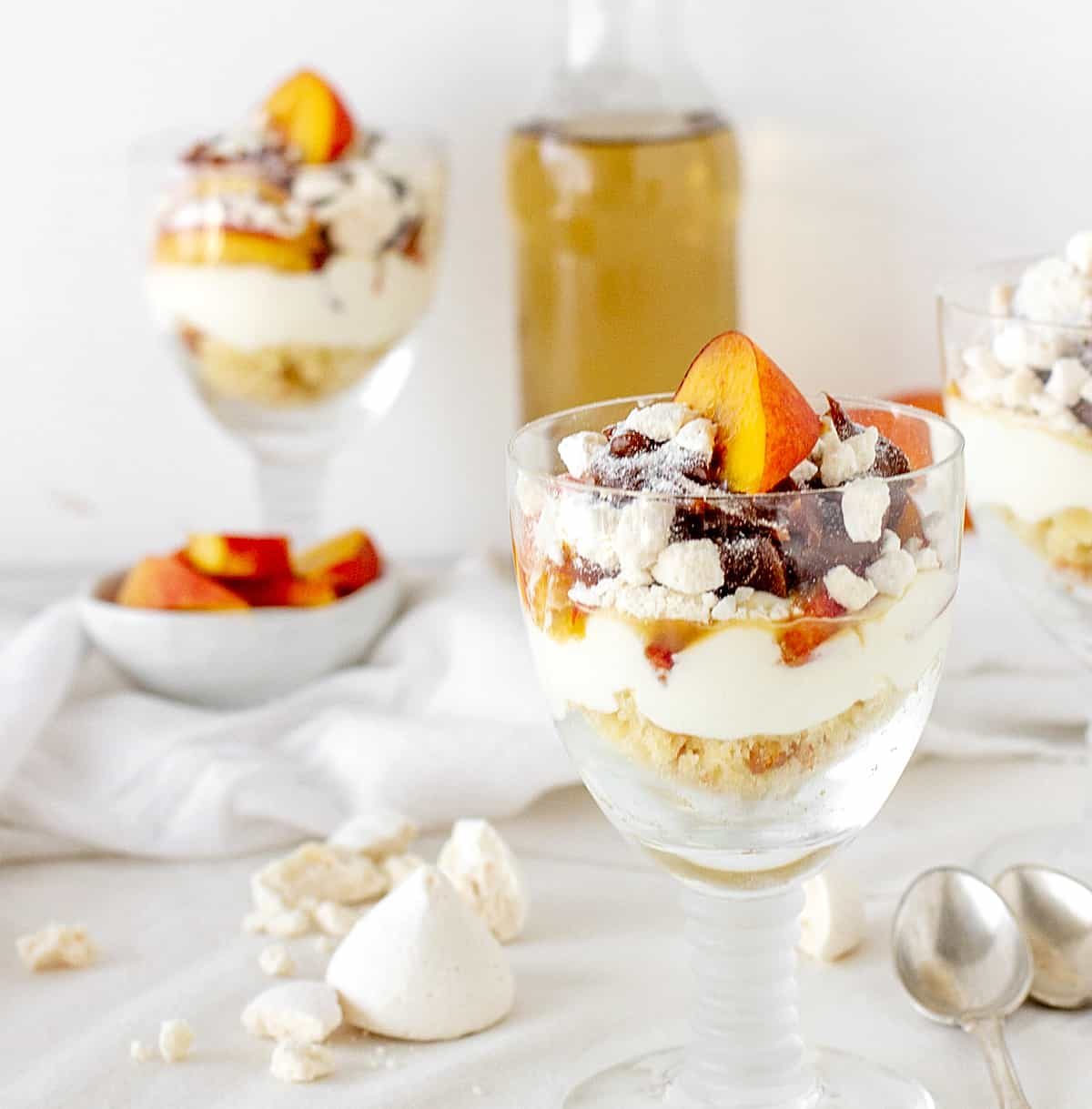 Long stem glasses with peaches and cream dessert, white surface, bottle and bowls in background