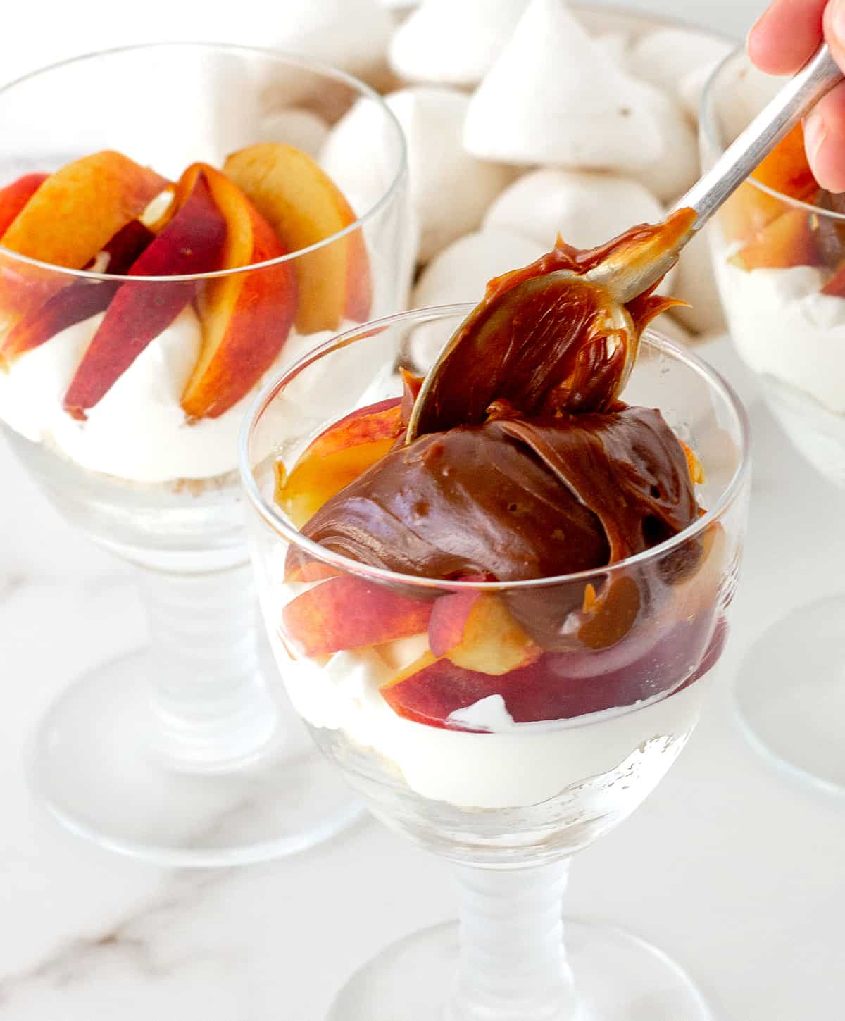 Dulce de leche added to peach trifle cups, white marble surface