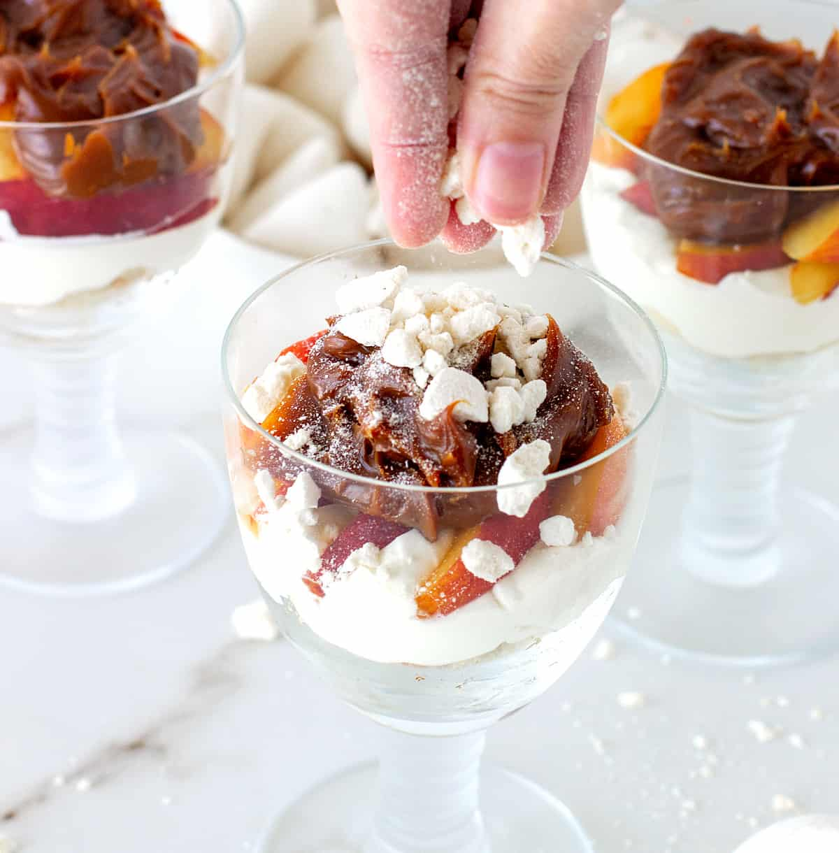 Crushed meringue added to glasses containing peach cream trifle on white marble table