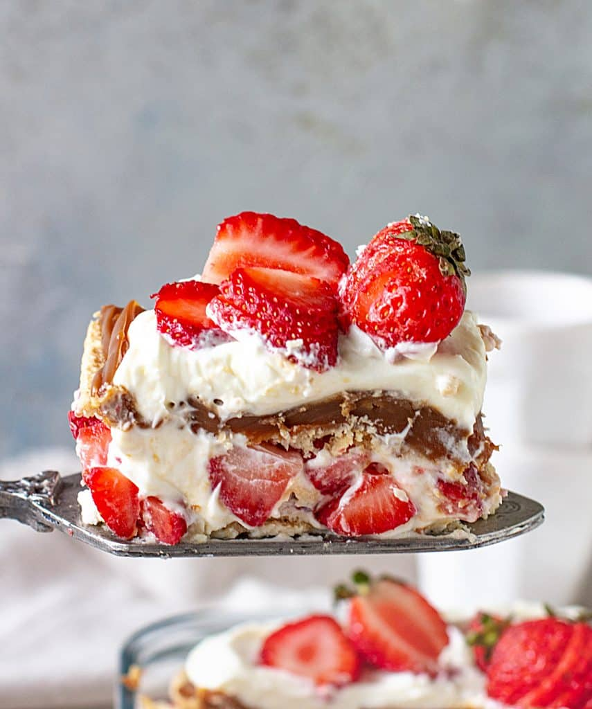Lifting a slice of no-bake strawberry cake with an antique cake server, grey background