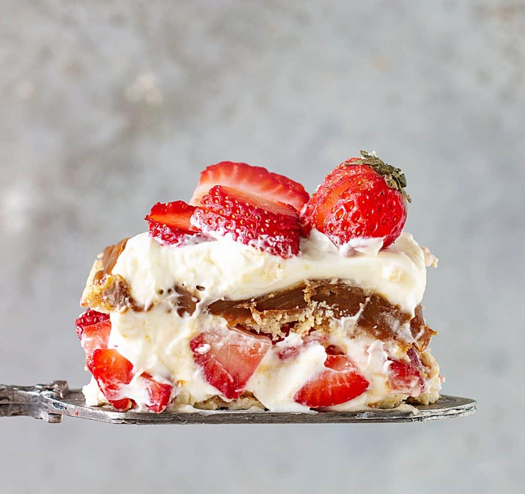 On a grey background, a cake server with a serving of strawberry topped dessert with cream and dulce de leche