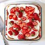 Serving on strawberry icebox cake on vintage cake server, greyish background