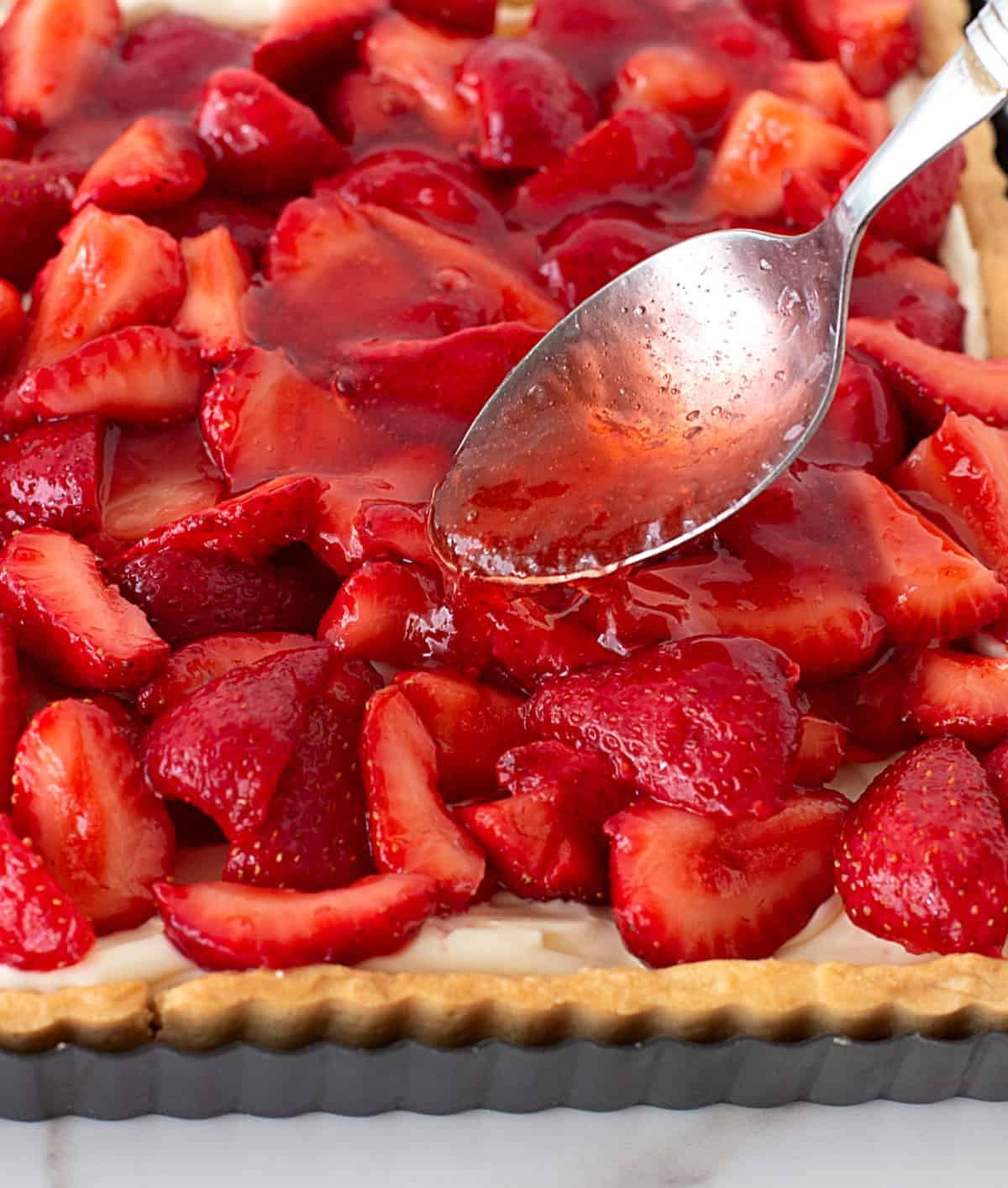 Adding strawberry jelly with spoon to tart topped with strawberries