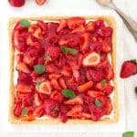 Square strawberry tart with mint leaves on a white surface