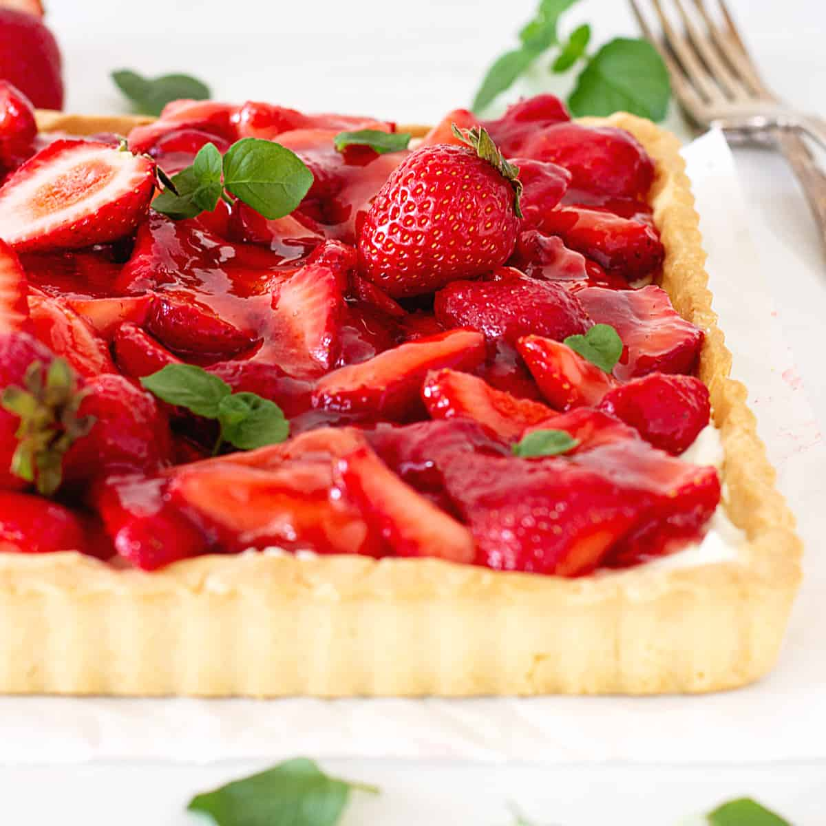 Partial slanted view of strawberry tart on a white surface, mint leaves on top