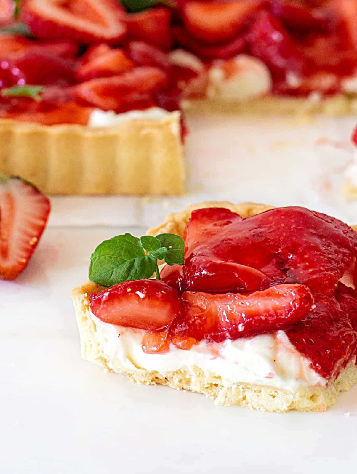 Close-up of square of strawberry cream tart, white surface, mint leaves
