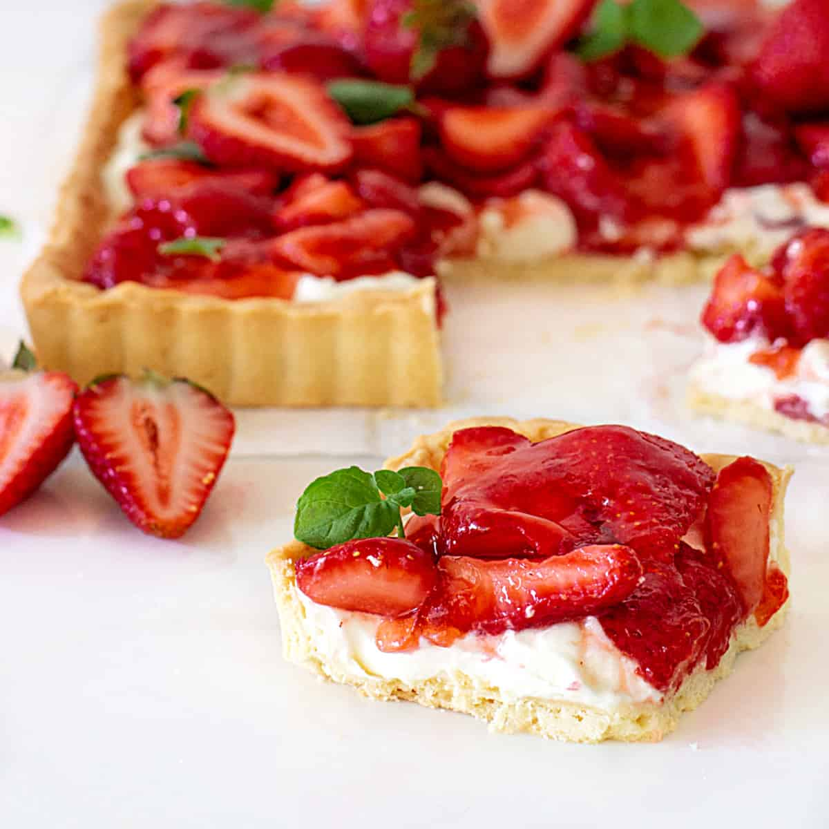 Slice of strawberry tart on white surface, rest of pie in background