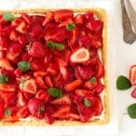 Partial view of strawberry tart on white surface, mint leaves and fork beside