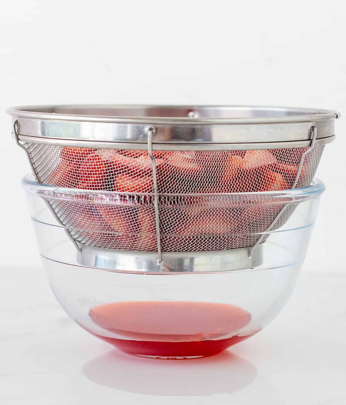 Metal colander with strawberries over a glass bowl, red juice dripping