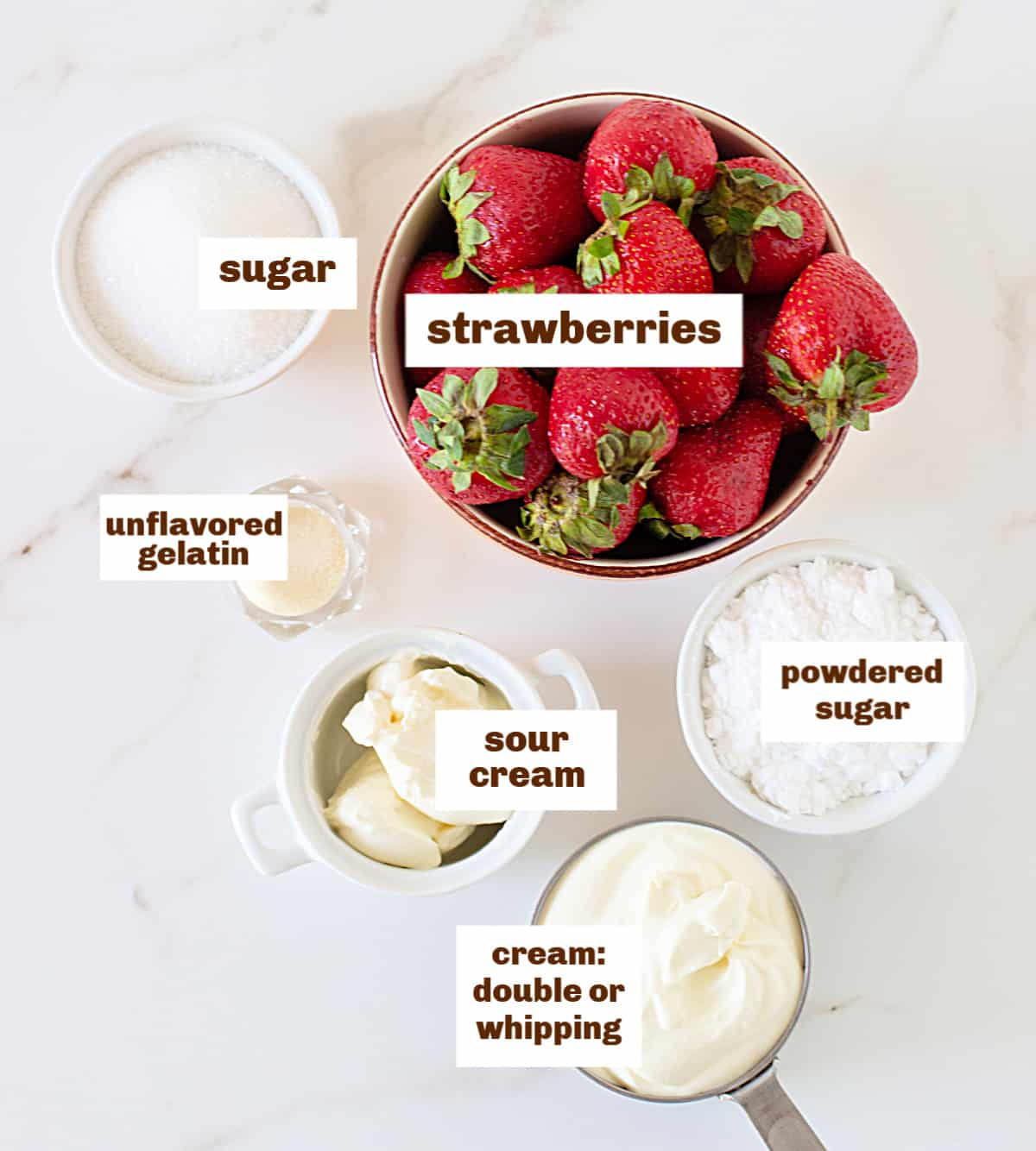 Bowls with strawberries, cream and sugars on a white table