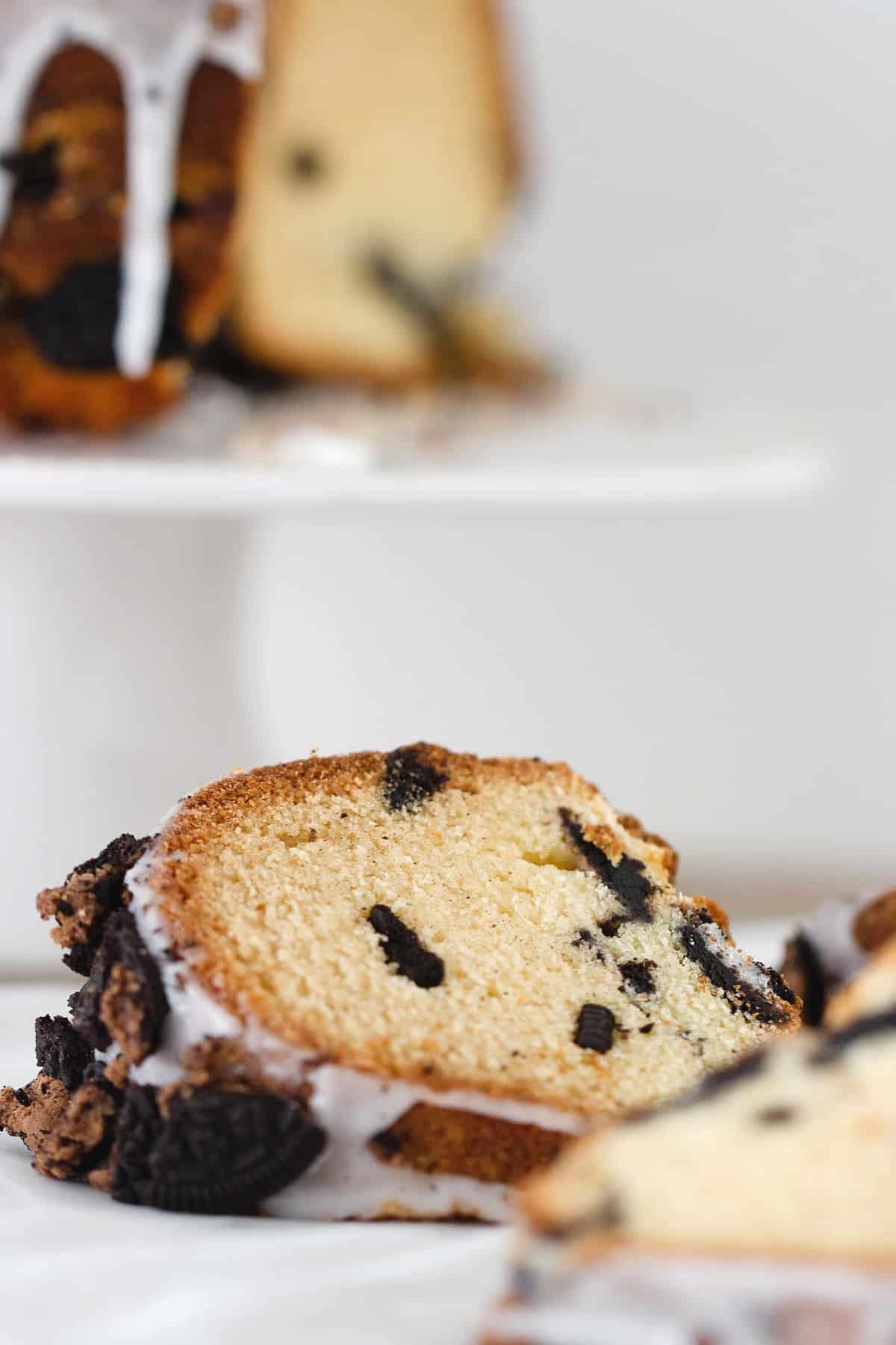 Bundt cookie cake slice, blurred cake on cake stand in background