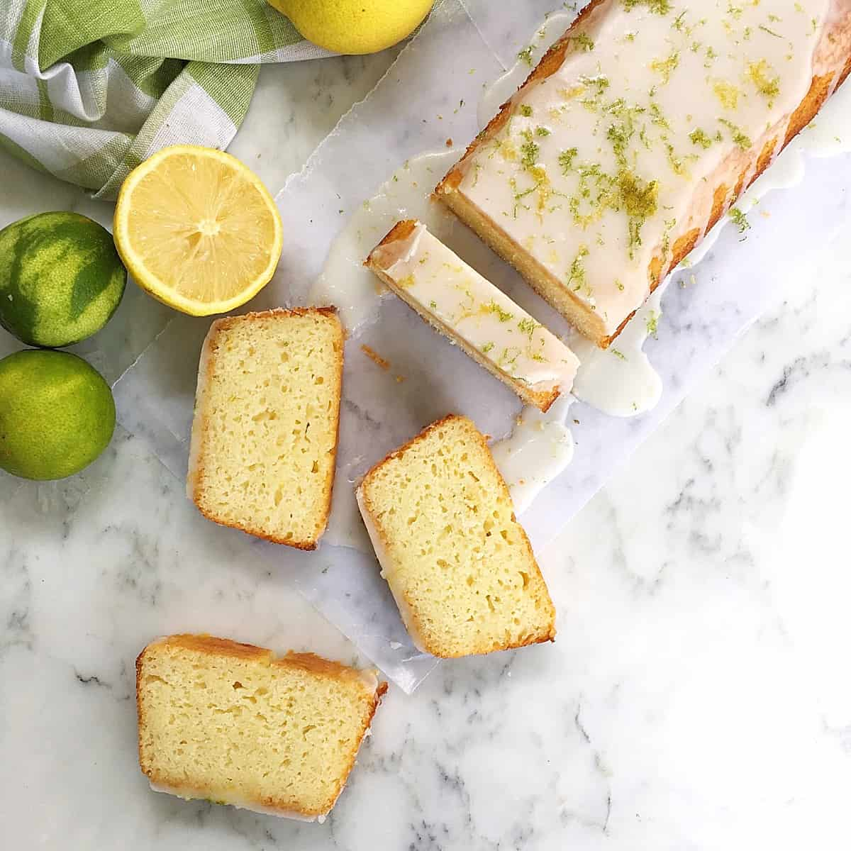 Half loaf cake on white marble surface, cut slices, lemons and limes around